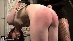 Fiery redhead in suspension gets her ass punished by her mistress