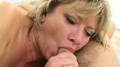 With a big cock filling her pussy, the blonde cougar sends another down her throat