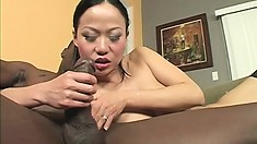 Asian cutie impales that little shaven twat of hers on a big black cock