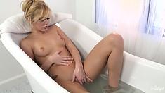 Skinny blonde hottie gets wet in the bathtub and masturbates