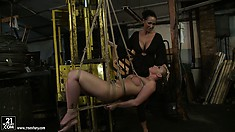 Naked slut hangs in the air while another female spreads her legs
