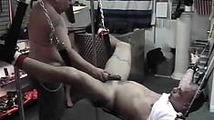 Strung up stud gets his ass fisted and dildoed before a handjob